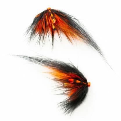 två laxfugor i mönster 'black & orange' bundna på tub med hårvinge i färgerna svart och orange