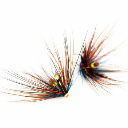 två laxfugor / havsöringsfluga i mönster 'thunder & lightning spey' bundna på tub i färgerna orange, svart och blå på vit bakgrund