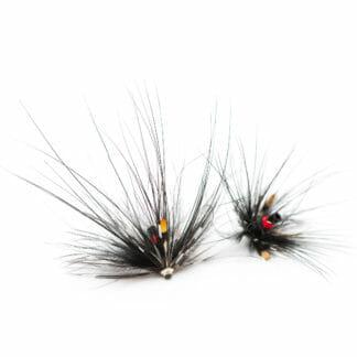 två laxfugor / havsöringsflugor på tub i mönster 'glödhäck spey' i färgerna svart och röd på vit bakgrund