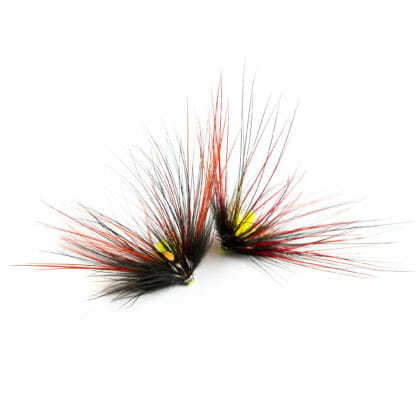 två laxfugor / havsöringsflugor i mönster 'willie gun spey' bundna på tub i färgerna svart, orange och gul på vit bakgrund
