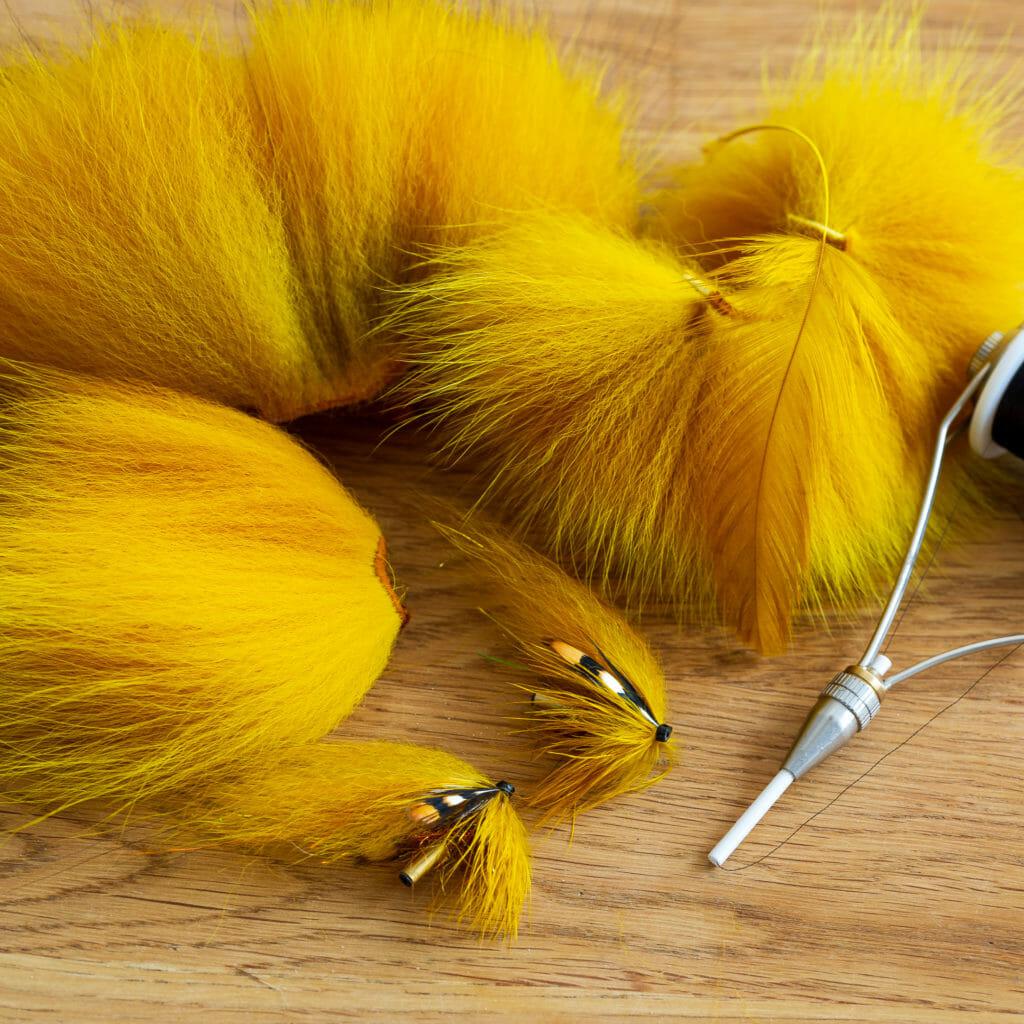 flugbindningsmaterial och laxflugor i gul banan färg